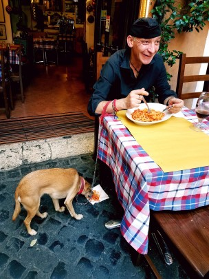 Old man in Rome feeding his dog